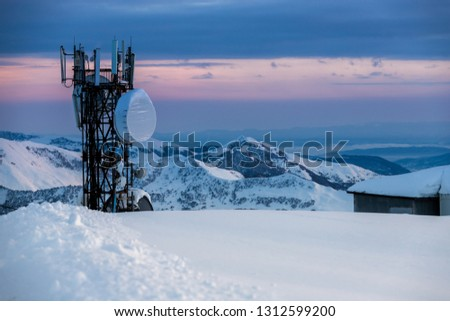 Communication tower with antennas and satellite dishes at background of a winter mountain landscape, at sunset. Gudauri, Georgia #1312599200