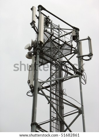 Communication tower with phone antennas over sky background