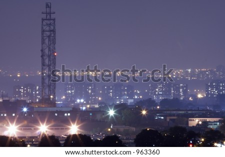 Communications mast at night with city lights.