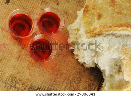 Communion bread and wine on a rustic surface.