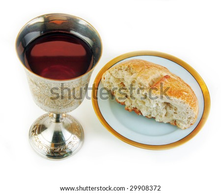 Communion bread and wine on a white surface.
