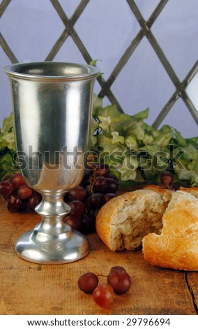 Communion bread and wine with grapes on a rustic surface in front of a leaded glass window.