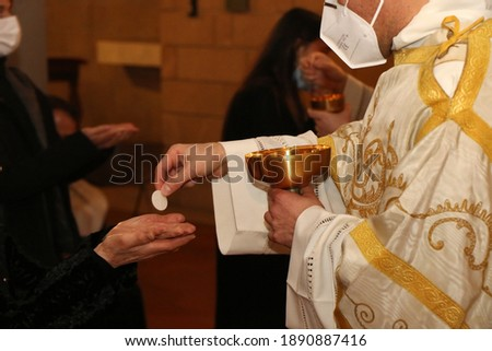 Communion rite during mass in a Catholic church. Priest wears surgical mask due to the Covid-19 pandemic