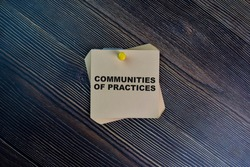 Communities of Practices write on sticky notes isolated on Wooden Table.