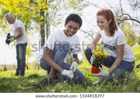 Community development. Jolly two volunteers planting flower and laughing