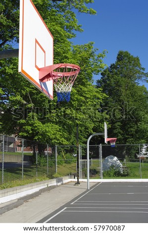 community outdoor basketball court with surrounding trees and sky prominent color blue grey white grey and red