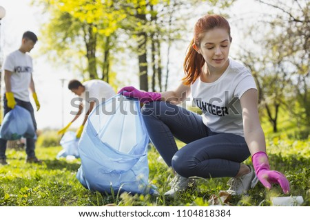 Community project. Beautiful female volunteer looking down while gathering rubbish