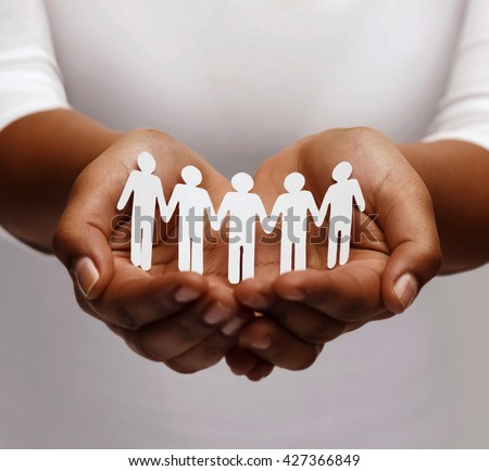 community, unity and charity concept - african american female hands holding and showing paper people team