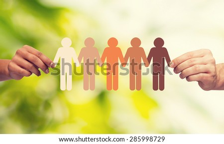 community, unity, people and support concept - couple hands holding paper chain multiracial people over green background Stock fotó ©
