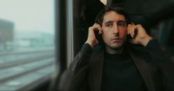 Commuter man putting on headphones while riding train and looking out window