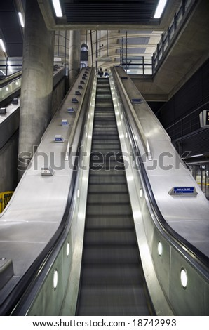 Commuters at the top of an escalator in underground railway station