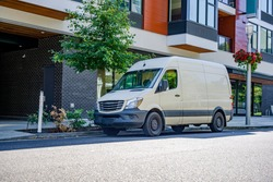 Compact cargo mini van for delivery and small business services standing on the urban city street with urban multi level residential apartment building