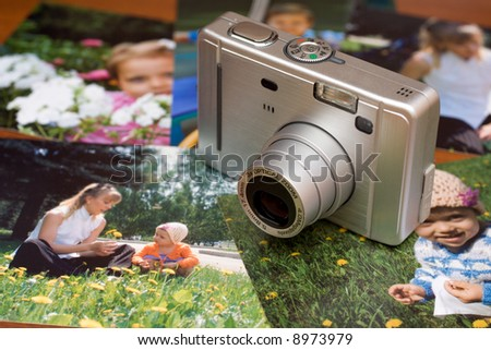 Compact digital camera and photos on the table