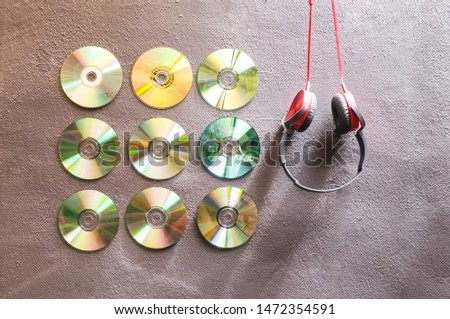 Compact discs displayed on grey wall