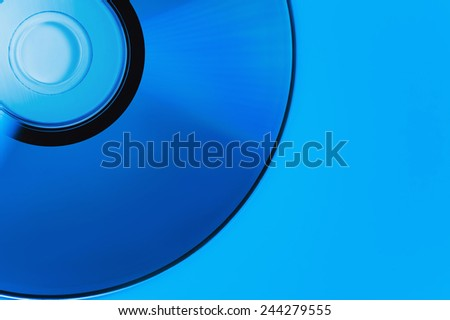 compact disk on blue backgrounds. This colour not computer effect. It is dark blue illumination lamp. Soft focus