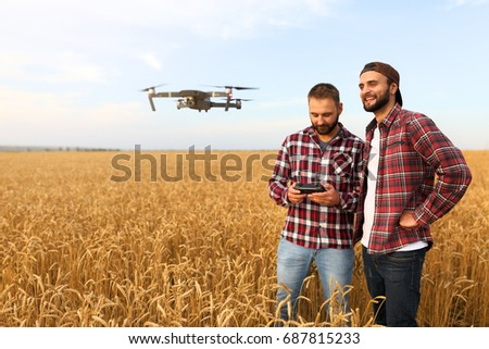 Shutterstock Compact drone hovers in front of two hipster men. Quad copter flies near pilot. Farmer and agronomist exploring harvest vith innovative technology taking aerial photos and videos from above