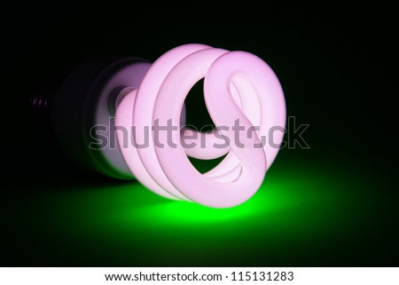 Compact fluorescent (CFL) bulb on green background - stock photo