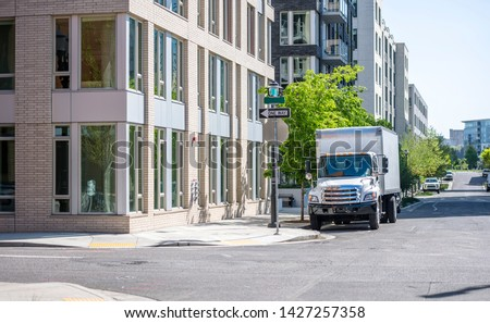 Compact rig semi truck with box trailer for moving to new apartments and local deliveries standing on the city street with multilevel apartment buildings for loading goods #1427257358