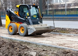 Compact road grader on a construction site is leveling a sandy base on a sidewalk path under construction. Light blur in motion, city road background.