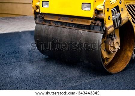 Compact steamroller flatten out the asphalt.