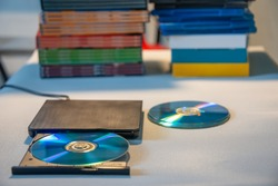 Compact stylish video player for CD and DVD disks with a pile of many TV series movie discs in background