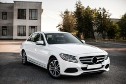 Compact white executive car, with beautiful wheels, large chrome grille.