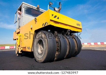 Compactor - Pneumatic Tyred Roller during asphalt paving. New road construction