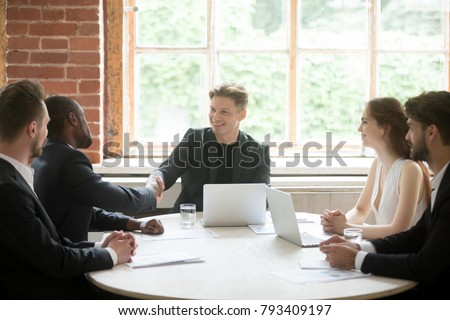 Company boss handshaking happy african employee, friendly ceo welcoming greeting promoting congratulating black businessman joining team at group meeting, executive and new hire member shaking hands