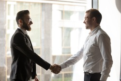 Company boss welcoming corporate client or multi-ethnic arabian european colleagues met at office hallway greet each other shaking hands express respect and nice to meet you friendly relations concept