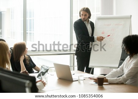 Company executive or business coach presenting new client management strategy to project team at board meeting, serious businessman giving presentation marketing training working with flip chart #1085354006