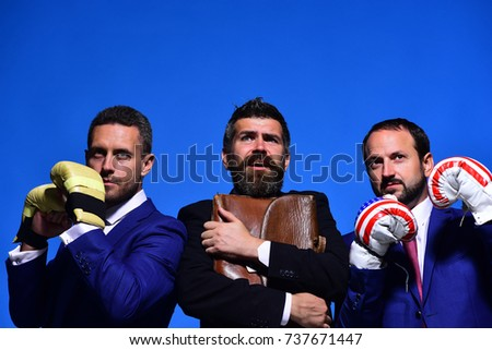 Company fights for business leadership. Businessmen and worker with strict and scared faces on blue background. Business conflict concept. Bosses wear boxing gloves, office manager holds case #737671447