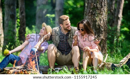 Company friends relaxing and having snack picnic nature background. Company hikers relaxing at picnic forest background. Camping and hiking. Halt for snack during hiking. Relax and fun in nature.