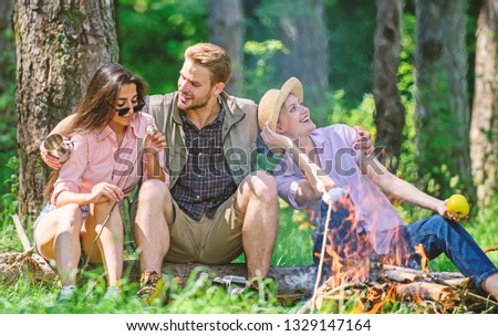 Company friends relaxing and having snack picnic nature background. Company hikers relaxing at picnic forest background. Camping and hiking. Halt for snack during hiking. Relax in nature environment.