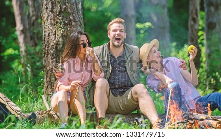Company friends relaxing and having snack picnic nature background. Halt for snack during hiking. Company hikers relaxing at picnic forest background. Camping and hiking. Relax and fun in nature.