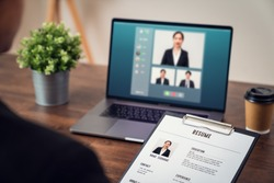 Company HR is holding a resume application in hand. Video calling, chatting and interviewing online jobs via digital laptop, Technology network saves time and is easy to coordinate.