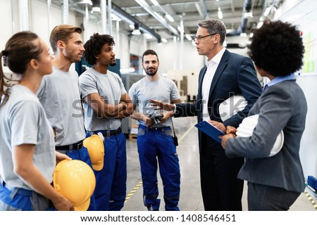 Company inspector taking a tour in industrial plant and communicating with group of workers.