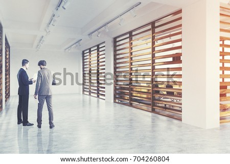 Company lobby interior with wooden and white walls and conference rooms with black chairs and tables. Side view, businessmen. 3d rendering mock up toned image