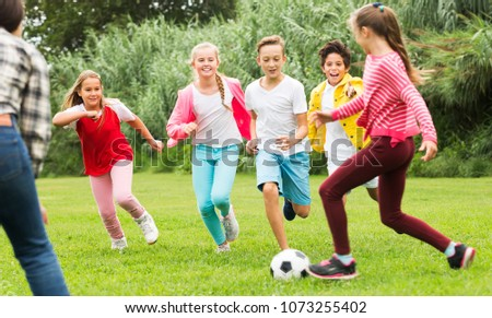 Company of cheerful kids playing football on the playground in park