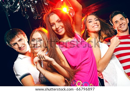 Company of cheerful teens enjoying themselves while dancing at disco