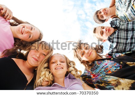 Company of excited teens hugging
