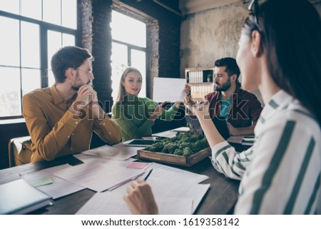 Company of four nice attractive professional skilled people manager agent broker sitting around table desktop discussing terms agreement at industrial loft interior style work place station office
