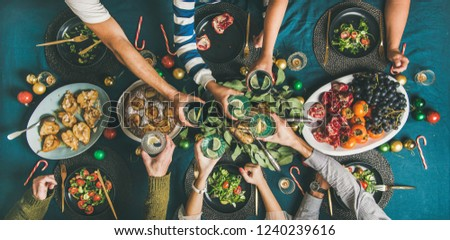 Company of friends or family gathering for Christmas or New Year party dinner at festive table. Flat-lay of human hands holding glasses with drinks, feasting and celebrating holiday together, top view