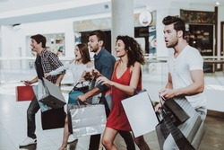 Company of Friends Shopping in Mall with Packages. Shopping Concept. Girl in Red Dress. Woman in White Shirt. Black Friday Concept. Exited Young People. Modern Market. Packs in Hands.