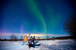 Company of friends tourist looks aurora northern lights night at forest, soft focus.