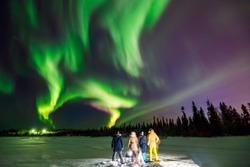 Company of friends tourist looks northern lights at edge forest. Soft focus blur effect