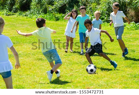 Company of glad children playing football on the playground in park Stock photo ©