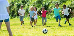 Company of glad children playing football on the playground in park. High quality photo