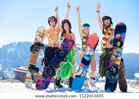 Company of happy smiling snowboarders sportsmen, girls in swimsuit, bra and skirt and men with bare torsos posing in snow with snowboards on background of blue sky and winter mountains ski resort. #1522653605