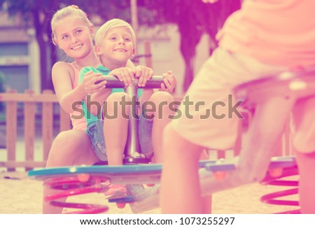 Stock Photo Company of kids are teetering on the swing on the playground.