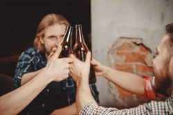 Company of old friends bearded young men drink beer at table in pub, jingle bottles. Brick wall background